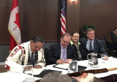 Kawacatoose First Nation Chief Darin Poorman and Aboriginal Affairs Minister Bernard Valcourt sign the document