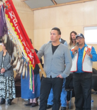 Facilitator Fred Campiou addresses the delegates of the Elders Counsel while Conway Kootenay holds the Eagle Staff