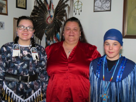 Marie Matchee is flanked by dancers Kennedy (16) and Roman (13) Brown-Matchee.  Kennedy made the beautiful jingle dress that she wore to the 2015 Ben Calf Robe Powwow as well as the regalia worn by her brother.  Article and photos by John Copley
