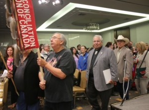 Alberta Elder Jerry Saddleback carries the TRC banner in Grand Entry on June 2, 2015, the day the Commissioners released the TRC Final Report summary in Ottawa. He is followed by the commissioners: Murray Sinclair, Wilton Littlechild and Marie Wilson.  Article by John Copley;   Photos by Terry Lusty