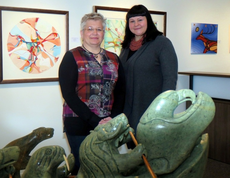 With prints by Alec Janvier and paintings by Aaron Paquette behind them and a Jonasie Faber sculpture in front, Jackie Bugera and assistant Hope Wright prepare for the 40th Anniversary exhibit at Bearclaw Gallery: Sept. 26 - Oct. 8