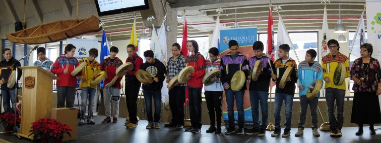 The Amiskwaciy Drummers,  joined by teacher Terrace Mah and Elders Francis Whiskeyjack and Jeanette Lean (far right), perform during the school's 2015 Christmas Feast.