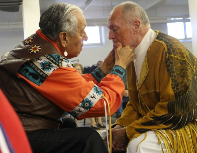 kanai Elder Martin EagleChild prepares Father Jim Holland for the headdress ceremony.