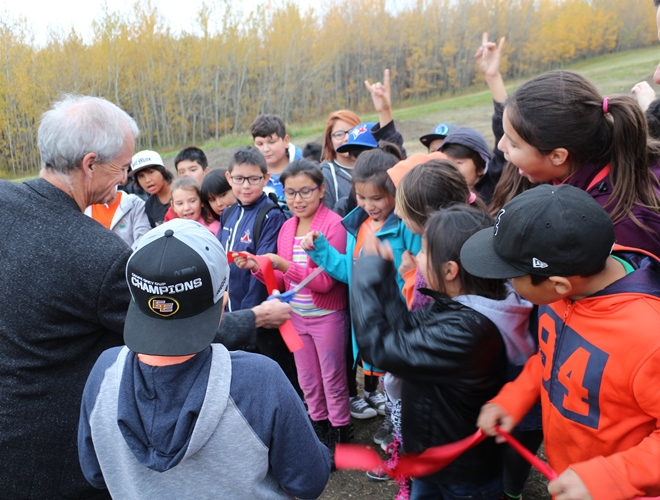 Bike Park organizer Don Patterson cuts the ribbon on September 30, opening the Enoch Bike Park as Kitaskinaw students cheer him on.