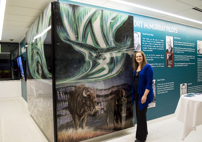 Amy Keller-Rempp poses with her installation at the Fort McMurray Airport.