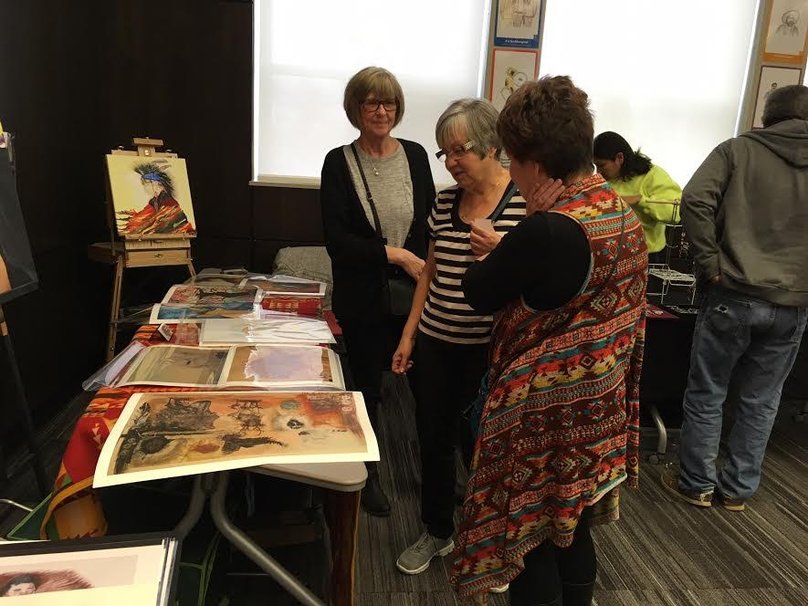 Visitors look over some of the artwork available at the crafts booth.
